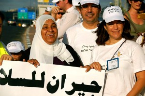 "Women and men from Awareness For You hold a protest sign with the message ""neighbors for peace"""